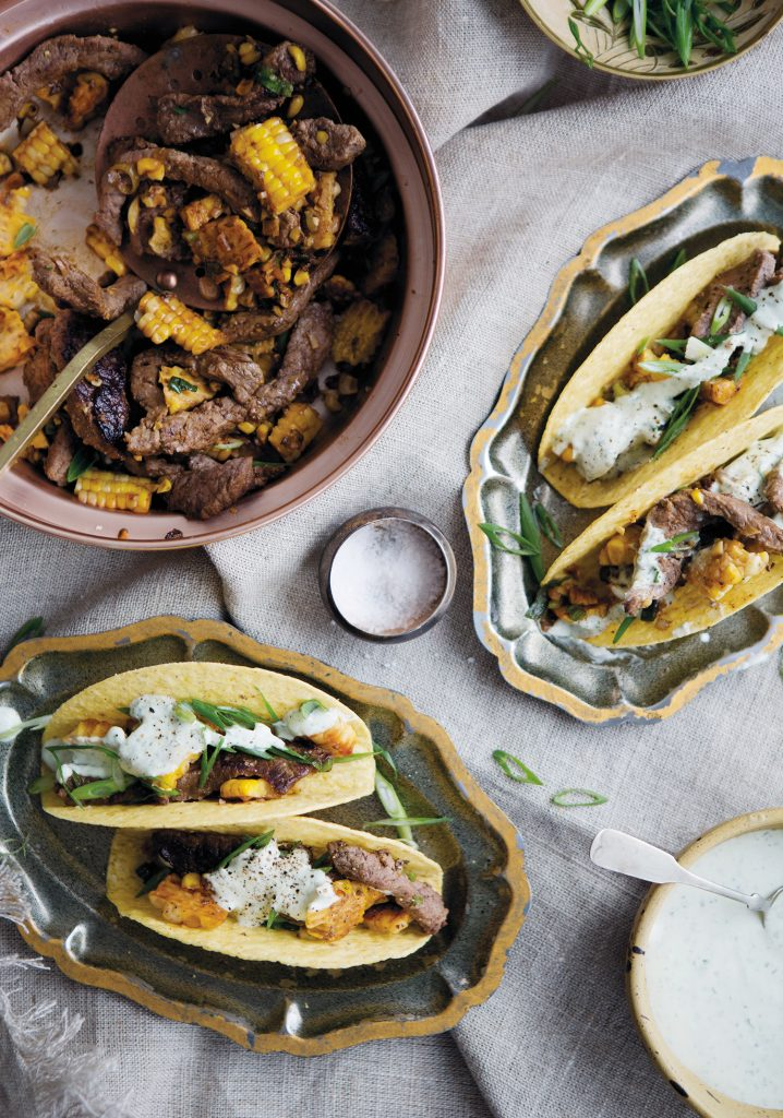 Beef and corn tacos with pesto sour cream