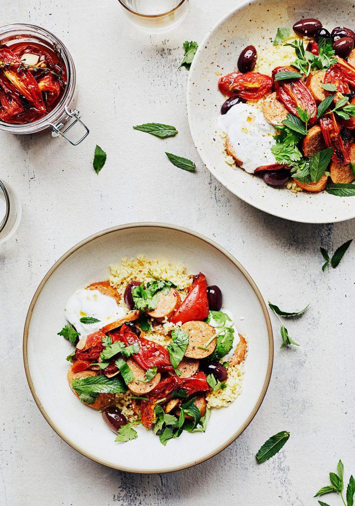 Couscous aux tomates confites, saucisses, olives & herbes fraîches