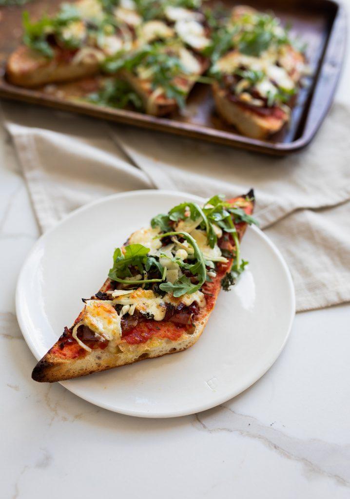 Pizza sur baguette au prosciutto, au chorizo, au chèvre & à la roquette